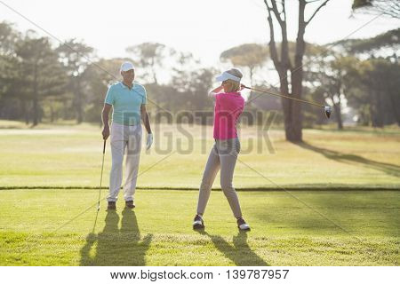 Full length of mature golfer playing by man standing on field