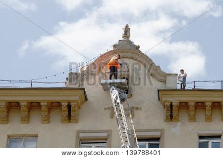 RUSSIA MOSCOW - JUNE 18 2015: Team of construction workers are reconstructing the facade of building in Moscow