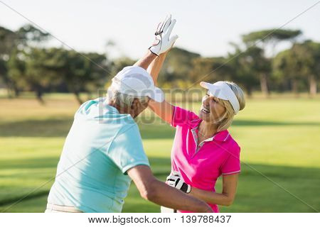 Cheerful golfer couple giving high five while standing on field