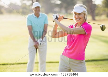 Portrait of confident mature woman carrying golf club by man standing on field