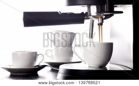 Close-up of espresso pouring from coffee machine. Group of cups on white background.