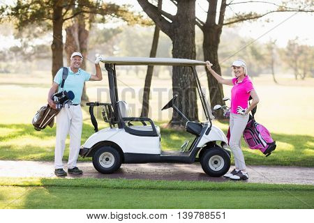 Portrait of smiling mature golfer couple standing by golf buggy