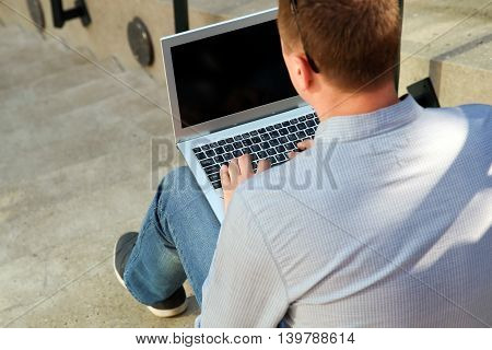 business man working with a laptop sitting outside