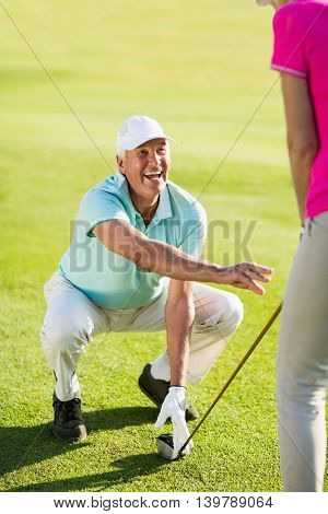 Smiling mature golfer man crouching while teaching woman standing on field