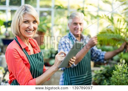 Portrait of happy woman using digital tablet while man working at greenhouse