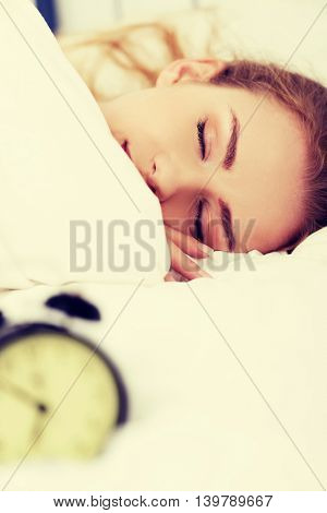 Beautiful sleeping woman with alarm clock.