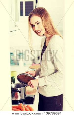 Beautiful caucasian woman standing in kitchen and cooking.