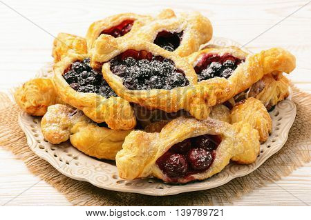 Puff pastries with cherries and blueberries .