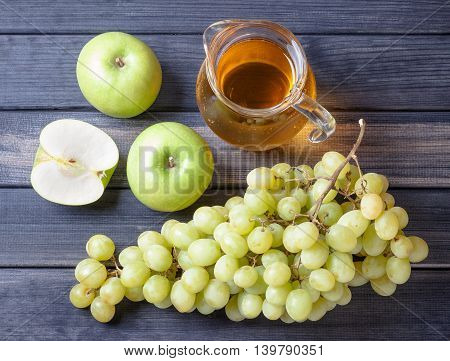 Apple and grapes on wood table, a pitcher of juice, still life