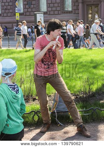 St. Petersburg, Russia - 9 May, The man playing the flute, 9 May, 2016. Vacationers people on the lawns and gardens in the city.