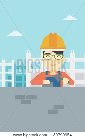 A n asian bricklayer in uniform and hard hat. Bricklayer working with a spatula and a brick in hands on construction site. Vector flat design illustration. Vertical layout.