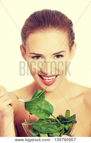 Woman eating lettuce from a bowl wit