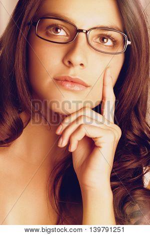Beautiful thinking woman wearing glasses