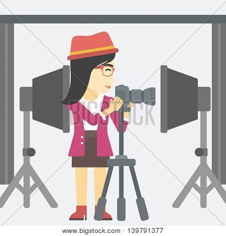 An asian young photographer working with camera on a tripod in photo studio. Woman taking photo with professional digital camera in the studio. Vector flat design illustration. Square layout.