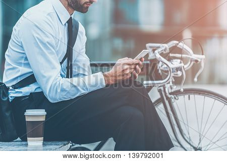 Sending business message. Cropped image of young businessman holding mobile phone while sitting near his bicycle outdoors