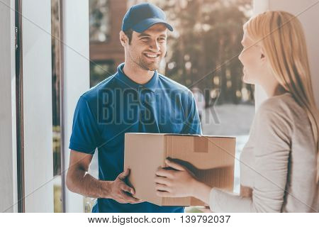Perfect delivery. Cheerful young delivery man giving a cardboard box to young woman while standing at the entrance of her apartment