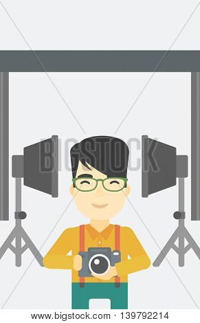 An asian young photographer holding a camera in photo studio. Photographer using camera in the studio. Woman taking photo with digital camera. Vector flat design illustration. Vertical layout.