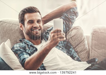 Good news! Cheerful young man holding mobile phone and smiling while lying on sofa