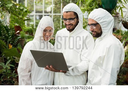 Scientists wearing clean suit discussing over laptop at greenhouse