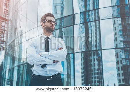 Confident businessman. Low angle view of confident young businessman keeping arms crossed and looking away while standing outdoors with office building in the background