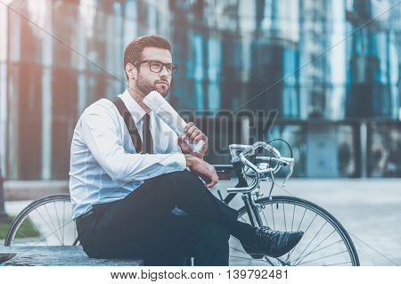 Thinking about solution. Side view of thoughtful young businessman holding newspaper and looking away while sitting near his bicycle with office building in the background