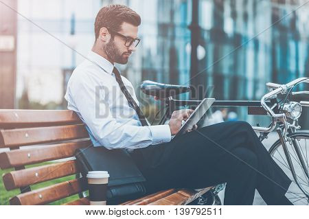 Always connected. Side view of confident young businessman working on digital tablet while sitting on the bench near his bicycle with office building in the background