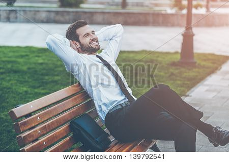 It is a beautiful day! Top view of happy young businessman keeping eyes closed and holding hands behind head while sitting on the bench outdoors
