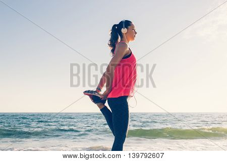 Sport Girl On The Beach In Headphones Does Sports Exercises In The Morning
