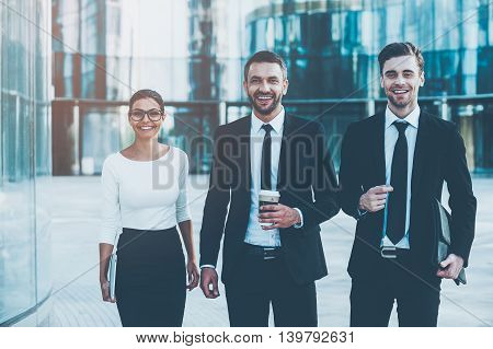 Business people on the go. Three cheerful young business people looking at camera and smiling while standing outdoors
