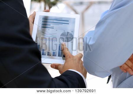 Image of two young businessmen using touchpad with graphs