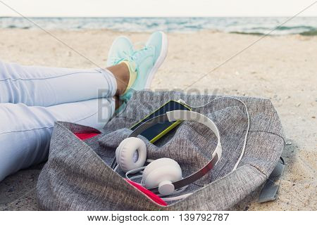 Women's legs in jeans and sneakers backpack headphones and smart phone the beach in summer