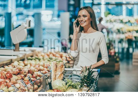 Woman in supermarket. Beautiful young woman talking on mobile phone and smiling while standing in a food store