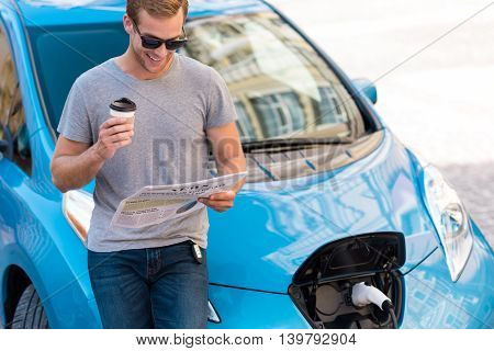 Beginning of the day. Confident young man readying a newspaper and drinking coffee while charging his hybrid car in the city