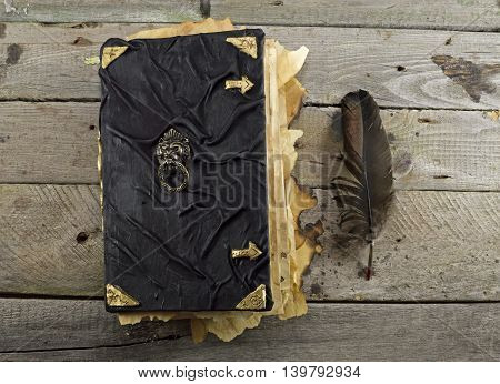 Black magic book with quill on wooden table