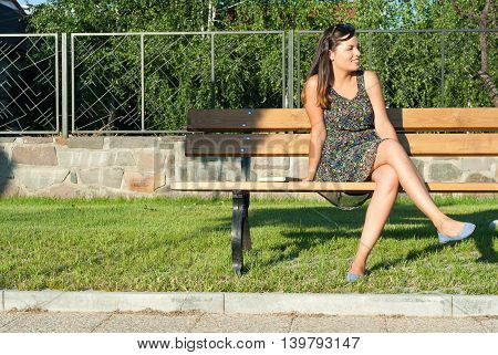 Girl Sitting On Bench In Park Looking Away
