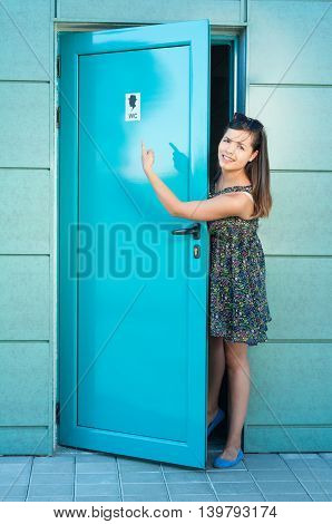 Girl Using Public Toilet Pointing The Sign