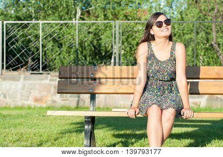 Lady Sitting On Bench And Enjoying Sunlight