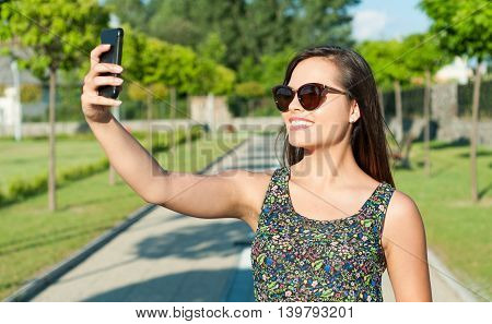 Pretty Girl Smiling And Taking Selfie In Park