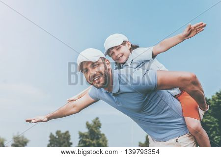 Carefree fun. Smiling young man piggybacking his son while standing outdoors