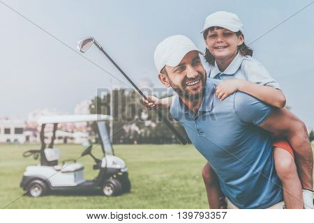 Great day to play golf! Cheerful young man piggybacking his son while standing on golf course