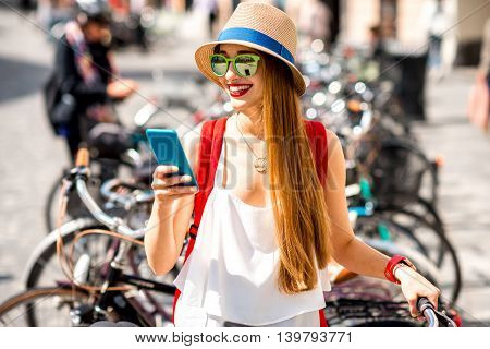 Young female tourist standing with mobile phone on the bicycle parking in the city. Bicycle rent with smart phnoe