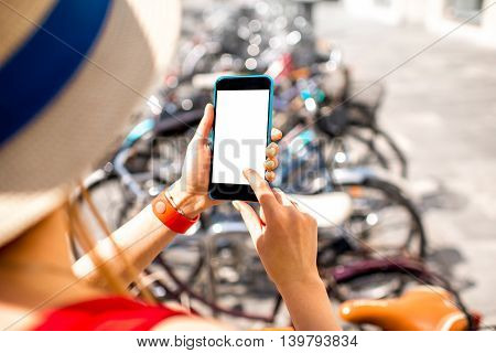 Woman holding smart phone with white screen on the bicycle parking background. Bicycle rent with smart phone. Mobile travel program