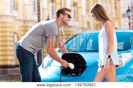 Look here. Smiling joyful man showing to his girlfriend how to plug a cable for charging a battery on their electric car