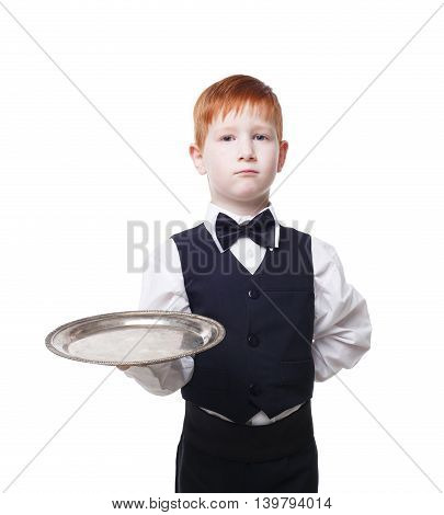 Little waiter stands with empty tray serving something. Redhead child boy in suit plays restaurant servant at blue background