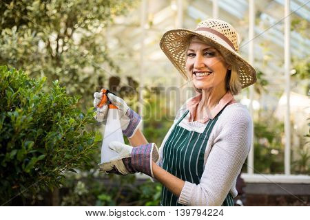 Portrait of happy female gardener spraying water on plants at greenhouse
