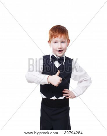 Little cute redhead boy in vest with bow tie shows thumb up. Portrait of well-dressed child in bow tie, approval, , satisfaction gesture. Kid isolated on white background