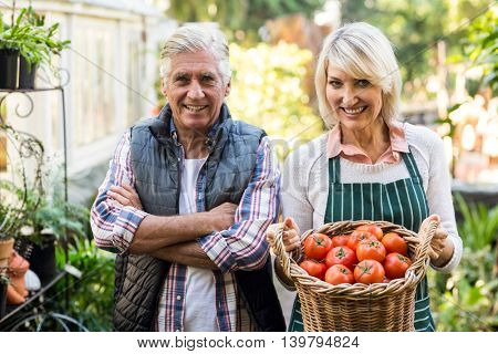Portrait of happy gardeners with tomato basket outside greenhouse
