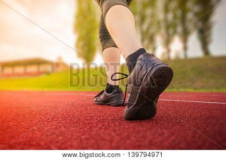 Runner or sprinter is running in stadium at evening.