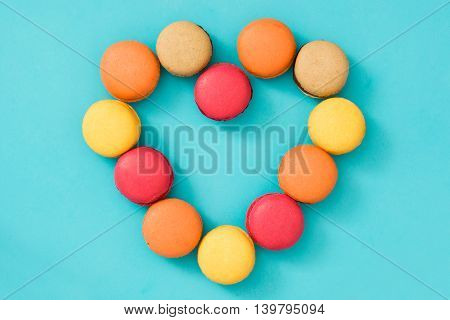 Colored macaroons with heart shape on blue background
