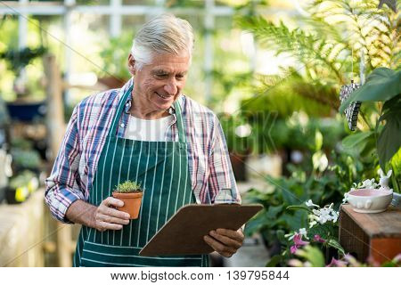 Male gardener smiling while holding potted plant and clipboard at greenhouse